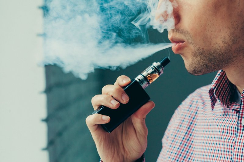 Bearded man vaping with electronic cigarette