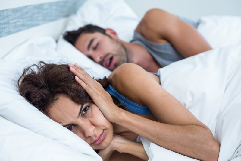 Annoyed woman covering her ears as man snores nearby