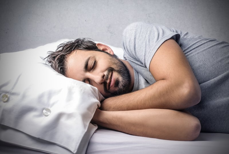 a man asleep on his side laying in bed