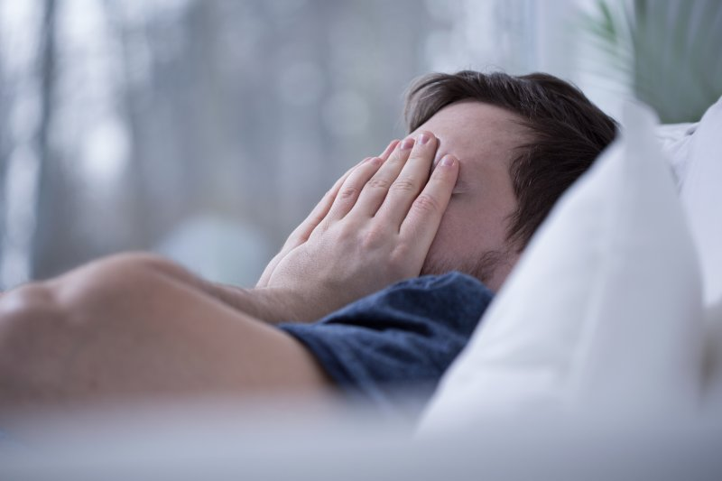 Man lying awake in bed covering his face